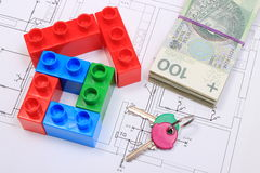 House of colorful building blocks, keys and banknotes on drawing of home. House shape of colorful building blocks, home keys and banknotes lying on construction Stock Photography