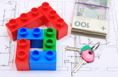 House of colorful building blocks, keys and banknotes on drawing of home. House shape of colorful building blocks, home keys and banknotes lying on construction Royalty Free Stock Images