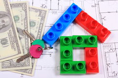House of colorful building blocks, keys and banknotes on drawing. House shape of colorful building blocks, home keys and banknotes lying on construction drawing Royalty Free Stock Photography