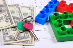 House of colorful building blocks, keys and banknotes on drawing. House shape of colorful building blocks, home keys and banknotes lying on construction drawing Stock Image