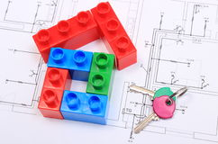 House of colorful building blocks, keys on drawing of home. House shape of colorful building blocks and home keys lying on construction drawing of house, concept Stock Photos