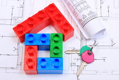 House of colorful building blocks, keys and drawings. House of colorful building blocks, home keys and electrical diagrams on construction drawing of house Stock Photos