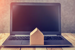 House concept with cardboard model next to black screen notebook Stock Photos
