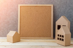 House concept with house shape cardboard on wooden floor and gre Royalty Free Stock Photography