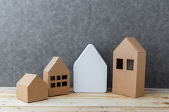 House concept with house shape cardboard on wooden floor and gre Royalty Free Stock Photos