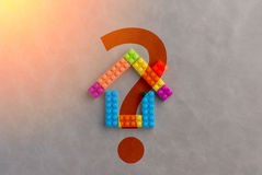 House concept with plastic blocks toy and question mark. jpg. House concept with plastic blocks toy and question mark on grey background. jpg stock photography