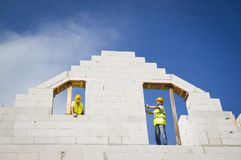 House construction. Builders are working on the top of house construction Royalty Free Stock Photo