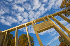 House Construction. House being constructed with clouds and trees in the background Stock Image
