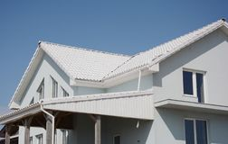 House Construction with energy efficiency white roof, unfinished balckony, veranda and roof gutter stock images