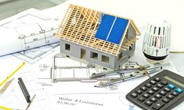 House with a construction plan and solar panel planning. House with a construction plan or bluebrint and solar panel planning royalty free stock photo