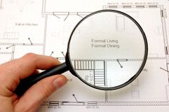 House construction plans. Examining house plans - hand with magnifying glass Royalty Free Stock Photography
