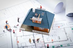 House construction project concept. building scale model and workers on blueprint royalty free stock photography
