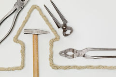 House Construction or Remodeling. Different hand tools and a rope in the shape of a house over a white background Stock Images