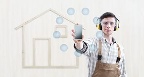 House construction renovation concept handyman carpenter man show the mobile phone with empty symbol icons, isolated with the royalty free stock photos