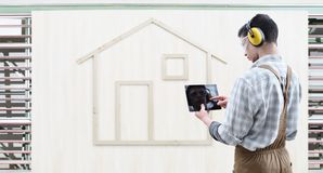 House construction renovation concept handyman carpenter man touch screen of digital tablet, isolated with the model of a wood stock photo