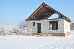 House construction in winter. Unfinished home roofing metal tiles construction. Roofing Construction in Winter stock image