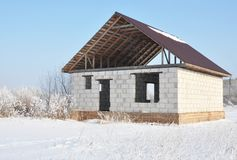House construction in winter. Unfinished home roofing metal tiles construction. Roofing Construction in Winter. Winter Home Build stock image