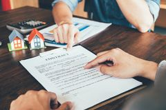 House Contract, Man reading a contract to purchase a home with a. Real estate agent, Loan and Payment Calculators ,Financial Calculators stock photo