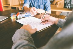 House Contract, Man signs a contract to purchase a home with a r. Eal estate agent, Loan and Payment Calculators ,Financial Calculators stock photography