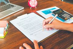 House Contract, Man signs a contract to purchase a home with a r. Eal estate agent, Loan and Payment Calculators ,Financial Calculators stock images