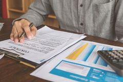 House Contract, Man signs a contract to purchase a home with a r. Eal estate agent, Loan and Payment Calculators ,Financial Calculators stock image