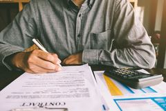 House Contract, Man signs a contract to purchase a home with a r. Eal estate agent, Loan and Payment Calculators ,Financial Calculators royalty free stock photography