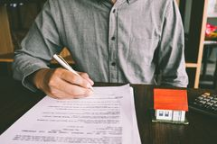 House Contract, Man signs a contract to purchase a home with a r. Eal estate agent, Loan and Payment Calculators ,Financial Calculators royalty free stock images
