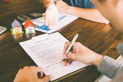 House Contract, Man signs a contract to purchase a home with a r. Eal estate agent, Loan and Payment Calculators ,Financial Calculators stock photos