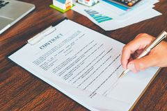 House Contract, Man signs a contract to purchase a home with a r. Eal estate agent, Loan and Payment Calculators ,Financial Calculators stock photo