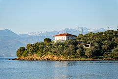 House on Corinthian Gulf Peninsular With Snow on Peloponnese Mountains. A Gulf of Corinth peninsular with a white house among olive trees, and Spring snow on the Stock Photography