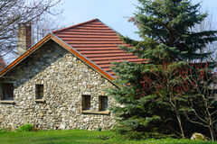 House in countryside. Exterior of stone house in countryside with spruce tree in foreground Stock Image