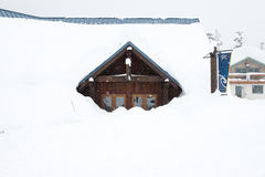 A house covered with thick snow on snowy day. Royalty Free Stock Image