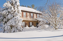 House covered in winter snow. Suburban house and front yard covered by drifted snow after a heavy winter snowstorm Royalty Free Stock Image