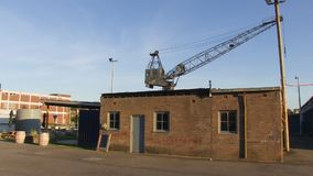 A house and a crane. A medium shot of a crane and a house