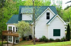 House with deck and patio. Side view of a vacant house with a wood deck and patio below, taken in early spring royalty free stock images