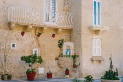 House decorated in catholic tradition, Malta. Mdina, Malta. Narrow street of ancient city with maltese house built of limestone. The house decorated in catholic Stock Image