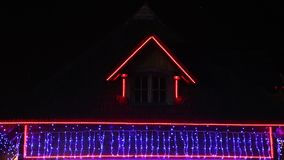 House decorated for Christmas. Christmas celebration - decorated house with colored lights outdoor stock video