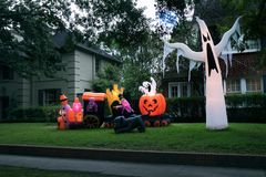 The house is decorated for Halloween: Inflatable train with the. Dead, big pumpkin, black cat huge and small ghost. Night, Houston, Texas, United States stock images