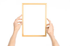 House decoration and Photo Frame topic: human hand holding a wooden picture frame isolated on a white background in the studio fir Royalty Free Stock Photography