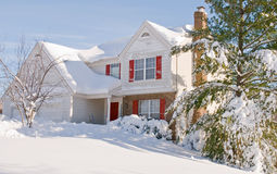 House in deep winter snow. Suburban house and front yard covered by deep, drifted snow after a heavy winter snowstorm Royalty Free Stock Image