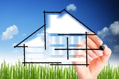 House design or build your own house. With woman hand drawing against blue sky Stock Photo