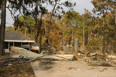 House destroyed by fire. Remains of house destroyed by fire with pine forest in background Royalty Free Stock Photo