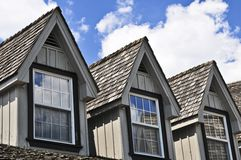 House detail. Window dormers on a house with wooden shingles on blue sky background Royalty Free Stock Photo