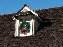 House detail with wooden roof and attic window. Attic window decorated for Christmas on large wooden shingle roof Royalty Free Stock Image