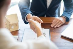 House developers agent or financial advisor and customers shaking hands after signing document making deal as successful. Agreement, contract with a firm royalty free stock photos