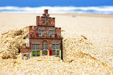House disappearing in the sand. Concept for real estate in crisis time Royalty Free Stock Image