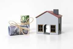 House and 100 dollars and euros banknotes. House and Rolled up 100 dollars and euros banknotes on a white background Stock Photography