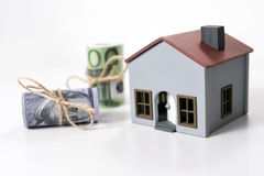 House and 100 dollars and euros banknotes. House and Rolled up 100 dollars and euros banknotes on a white background Stock Image