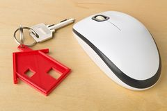 House door key with red house key chain pendant and computer mou. Se on wooden desk - online house rental or purchasing concept Royalty Free Stock Image
