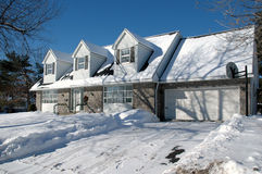 House with dormers in winter. Classic house style in snow Stock Photos